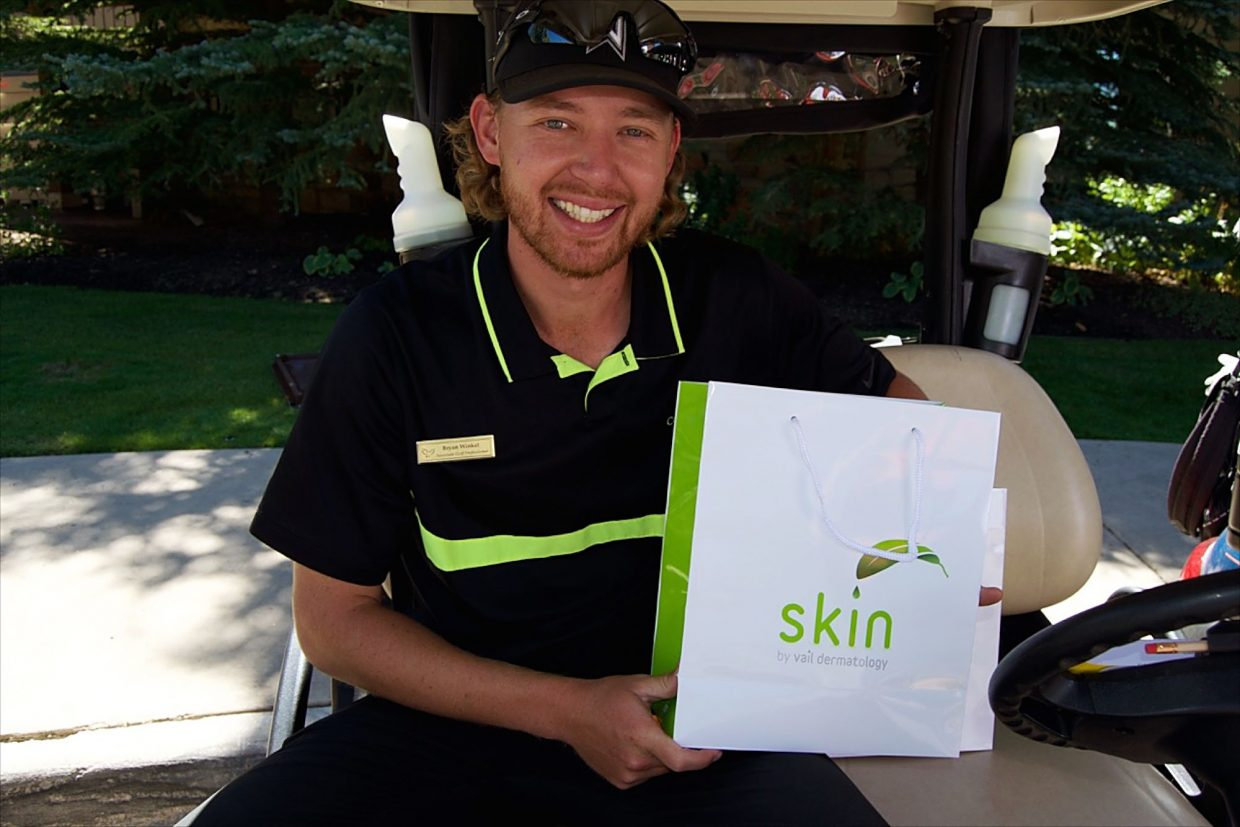 Valley Course at The Club at Cordillera associate golf professional Bryan Winkel displays a Skin by Vail Dermatology gift bag at the 2016 Summit Melanoma Golf Tournament.