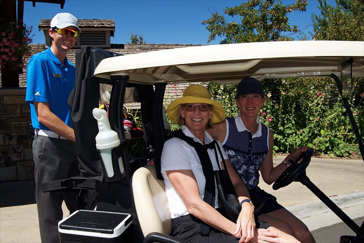 Megan Green and owner of Vail, Aspen and Breckenridge Dermatology Karen Nern, M.D., get ready to head out to play some golf in the 2016 Summit Melanoma Golf Tournament at the Valley Course at The Club at Cordillera as Brodie Leibrandt readies their cart.