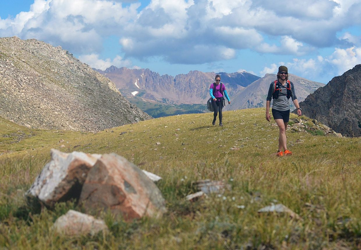 Local hikers Sara Skinner (purple) and Ben Trollinger hike on relatively smooth and forgiving terrain between Peak Four (12,866 feet) and Peak Five (12,855 feet) during an attempt of the Tenmile Traverse. The sheer, reddish face of the Gore Range is in the background.