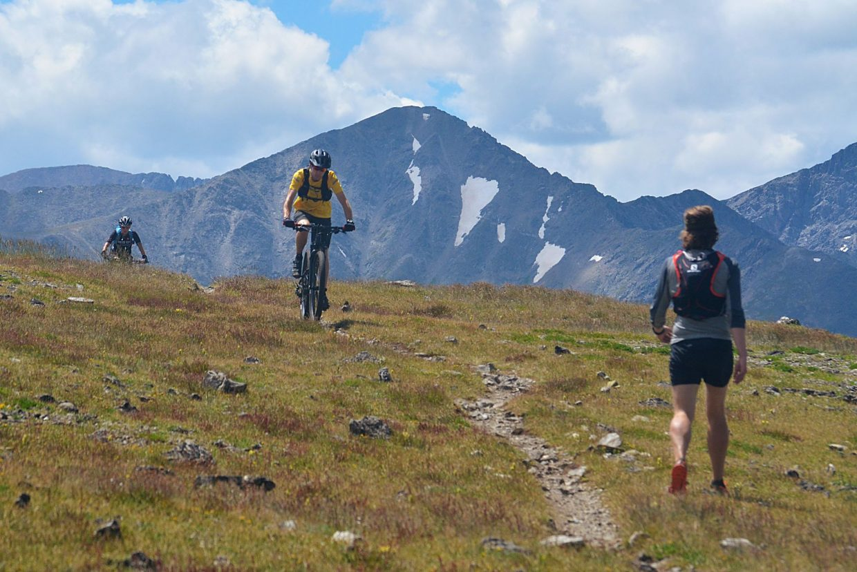 Summit Daily News managing editor Ben Trollinger (right) steps to the side of upper Wheeler Trail on the Tenmile Range as cyclists approach from Wheeler Pass. The Tenmile Traverse meets with occasional stretches of trail after leaving Peak One, but the most common route stays high on the cairn-marked ridgeline.