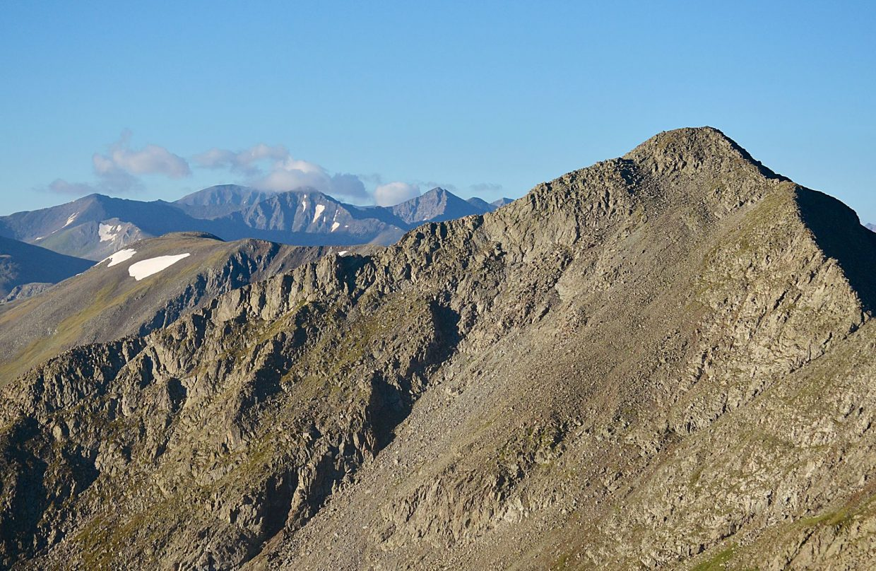 On a clear day, the Tenmile Traverse is relatively easy for routefinding thanks to a clear line of sight from one end to the other. Tenmile Peak (aka Peak Two 12,933 feet) is near on the right, with the flat north face of Quandary Peak (14,265 feet) far in the center background.