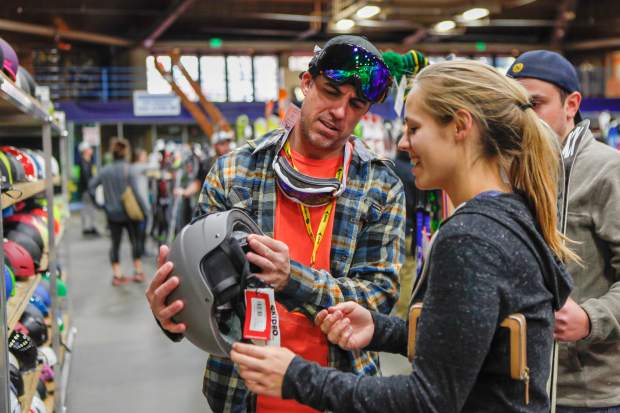 Brandi Bradley of East Vail gets some tips on picking out a helmet form Laurent Lebihan of Pheonix during the 47th annual Vail Ski and Snowboard Swap. Friday, at Dobson Ice Arena in Vai. Doors opened Friday for early-bird shopping at 5 p.m.