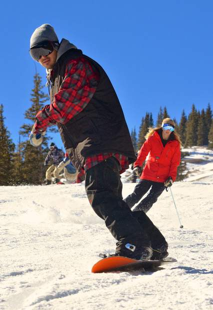 A snowboarder and skier wind down Crescendo on opening day at Breckenridge Ski Resort Nov. 19. More than 3,000 skiers and snowboarders came to Breck for top-to-bottom skiing on two runs: Crescendo and lower Springmeier.