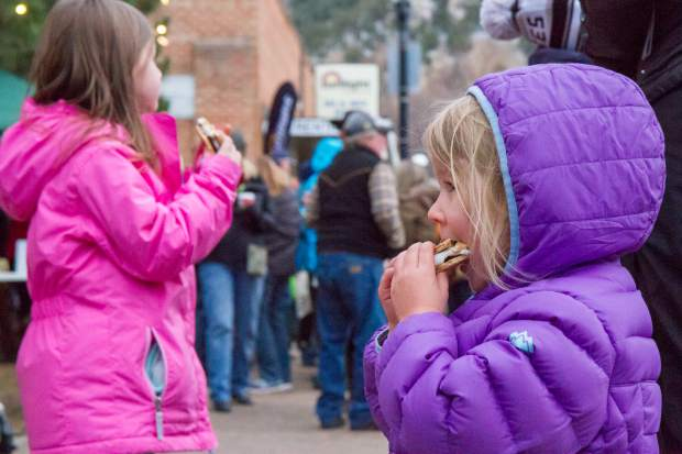 Three year old Elizabeth Kelly eats the smore she made in the fire pit at the welcoming of the U.S. Capitol Christmas tree event in Centennial Park.