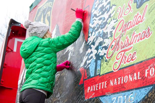 Ten-year-old Zoe Sheldrake signs the banner of the U.S. Capitol Christmas tree.