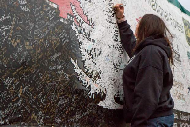 Victoria Vasquez (16) signs the banner on the truck carrying the Christmas tree headed to Washington DC.