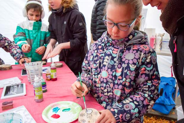 Tessa Lallier paints a block of wood at the welcoming of the U.S. Capitol Christmas tree event in downtown Glenwood Springs.
