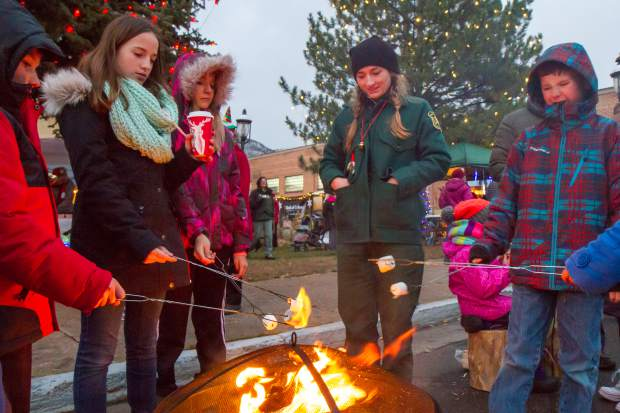 People gather around the warm pit to warm up during the welcoming of the U.S. Capitol Christmas tree event in Centennial Park.