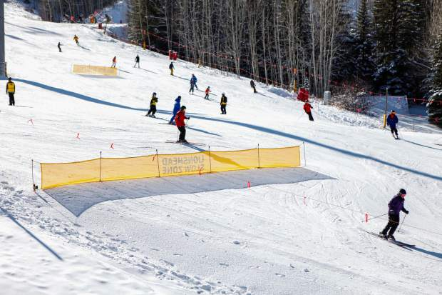 Skiers and riders make their way down to the base of Lionshead for Opening Day on Friday in Vail.