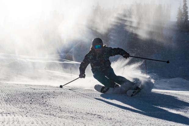 Will Feldman, of Denver, carves into the new season while snow guns blast snow behind him on Friday at Beaver Creek. The resort opened two days later than anticipated, but a change in weather should provide more terrain openings in the near future.