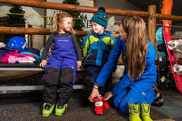 A ski instructor helps two young students get ready for a day on the slopes at Keystone Resort. Ski instructors say one of the most common problems for beginners is showing up for a day of skiing or riding without the right gear.
