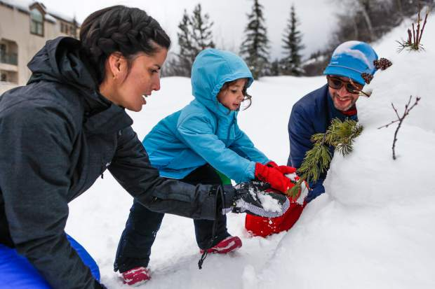 From left, Natalia Vidal, Lenna Torres, 3, and Jose Torres of Puerto Rico help Lenna build her first snowman on Tuesday in Beaver Creek. The family says they've been loving all the new snow.