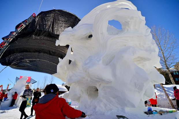 Passers-by stop as Zhaoqun du, with Team China, works under cover on a sea-inspired snow sculpture titled