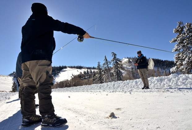 Noah Rawls, 14, of Texas (left) practices casting technique with Breckenridge Outfitters guide Chip Swanson near the Blue River tail waters below Dillon Dam. The stretch of the Blue is perfect for winter angling thanks to fast-moving water that rarely freezes and abundant prey like midges and Mysis shrimp.
