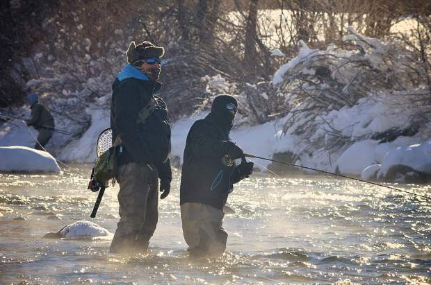 Local fly-fishing guide Chip Swanson (left) helps 14-year-old Noah Rawls with casting technique on a chilly morning on the Blue River outside of Silverthorne in December. Breckenridge Outfittes and other local fly-fishing guides host tours year-round on the Dillon Dam tail waters and other unfrozen sections of the Blue.