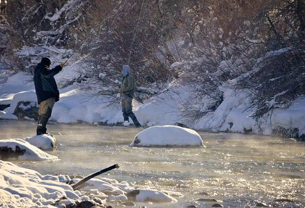 Ben Rawls, 38, of Texas (left) and another angler on the Blue River below the Dillon Dam in December. Rawls and his family joined two guides with Breckenridge Outfitters for an intro fly-fishing session, including fly selection, casting basics and more tailored for winter angling.