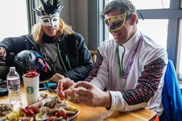 Gary Nordahl picks at what's left of the crawfish boil as Kristy Nordahl looks on during CarniVail on Saturday at Eagle's Nest at the top of Lionshead in Vail. The Mardi Gras celebration featured the crawfish boil, live music and giveaways.