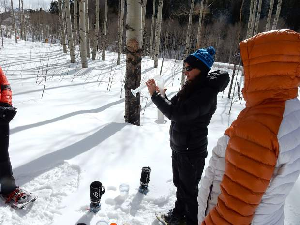 Liza Mitchell of the Roaring Fork Conservancy boils snow samples taken from different depths in the pit to demonstrate how the water density varies.