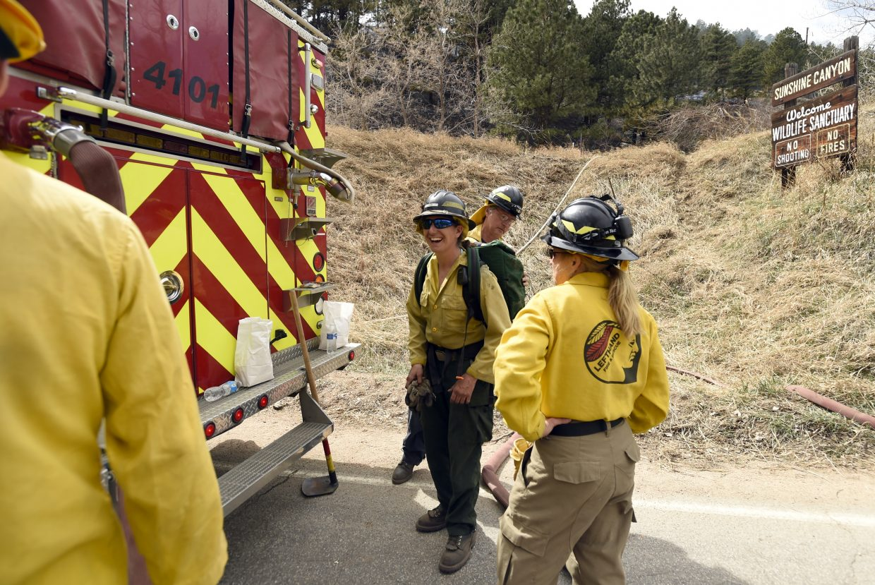 Lefthand Fire District firefighters, including Melissa Friess, at center, load supplies to take to crews battling the Sunshine Fire in the Sunshine canyon area of Boulder, Colo. on Sunday, March 19, 2017. The small wildfire forced people from their homes early Sunday and ignited dead trees that exploded into black plumes of smoke, authorities and residents said. (Jeremy Papasso/Daily Camera via AP)