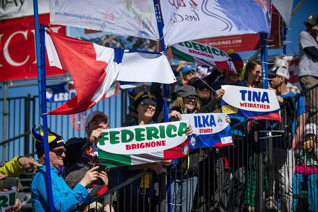 Fans hold signs supporting their athletes as they go up on the podium for the finalists of the Super-G races on Thursday.