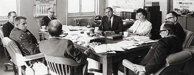 """The Colorado Mountain College Governing Board met on Jan. 7, 1966, two months after the college district was established. At the far end of the table, wearing glasses, is David Delaplane, then counterclockwise, Howard Clark (Summit County), David Barbee (Pitkin County), Dr. Leland Luchsinger (Colorado Department of Education), Pat Harvey (Lake County), Bill Stevens (Colorado Commission on Higher Education), Josephine """"Jody"""" Busby (Garfield County clerk who certified the votes) and Harold Koonce (Eagle County), who was selected as first board president. The persistence of these and other pioneers to build support enabled the college to open the first two CMC campuses – the West Campus in Spring Valley and the East Campus in Leadville – on Oct. 2, 1967. Photo Colorado Mountain College archives"""