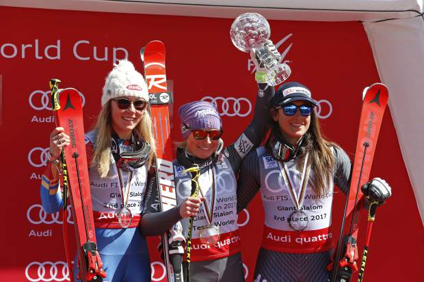 World Cup women's giant slalom overall champion France's Tessa Worley, center, celebrates beside second place overall finisher United States' Mikaela Shiffrin, left, and third place overall finisher Italy's Sofia Goggia after a women's World Cup giant slalom ski race Sunday, March 19, 2017, in Aspen, Colo. (AP Photo/Nathan Bilow)