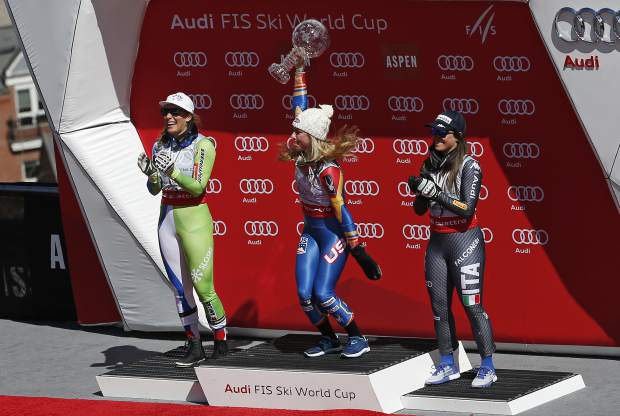 World Cup overall women's 2017 champion United States' Mikaela Shiffrin, center, holds up a crystal globe trophy beside second place overall finisher Slovenia's Ilka Stuhec, left, and third place overall finisher Italy's Sofia Goggia after a World Cup skiing race Sunday, March 19, 2017, in Aspen, Colo. (AP Photo/Brennan Linsley)
