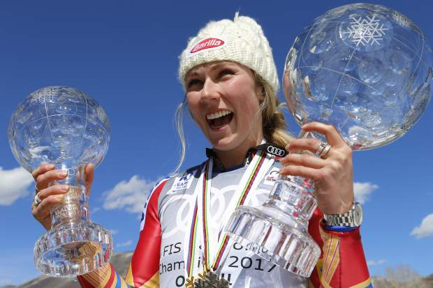 World Cup overall women's 2017 champion United States' Mikaela Shiffrin smiles as she holds up a crystal globe trophies after a World Cup skiing race Sunday, March 19, 2017, in Aspen, Colo. (AP Photo/Nathan Bilow)