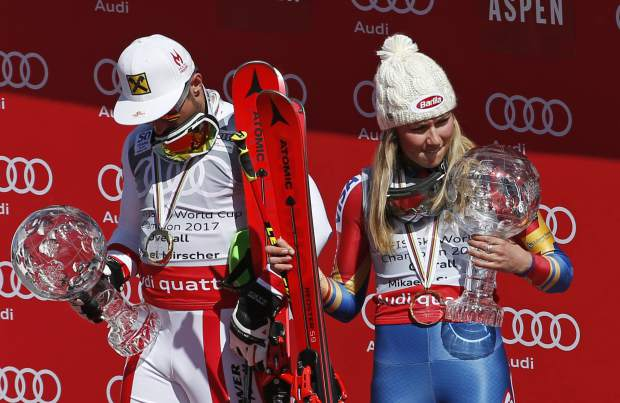 World Cup overall men's 2017 champion Austria's Marcel Hirscher, left, and World Cup overall women's 2017 champion United States' Mikaela Shiffrin hold their crystal globe trophies on the podium after a World Cup ski race Sunday, March 19, 2017, in Aspen, Colo.(AP Photo/Brennan Linsley)