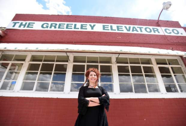 Heather Bean stands out front of the Greeley Elevator building Friday in downtown Greeley. The building will be renovated and transformed into the new distillery for Syntax Spirits.