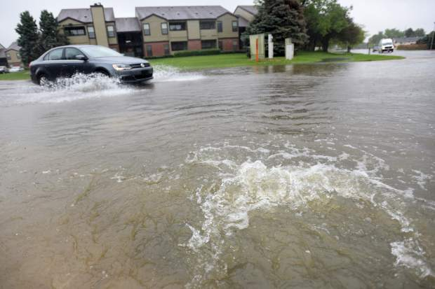 A car slows down to drive through the growing pool of water at 50th Avenue and 11th Street in west Greeley. According to the National Weather Service, Greeley could see up to anotehr 3 inches of accumulation by Friday.