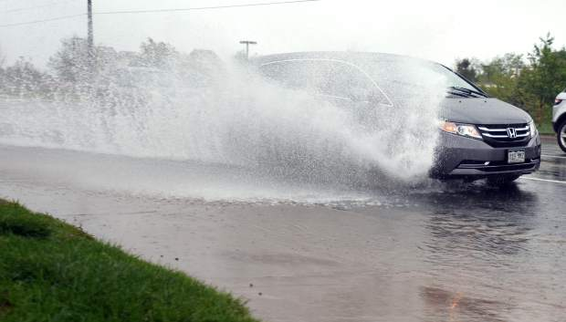 Water sprays up as a car passes through a large puddle along 47th Avenue in west Greeley.
