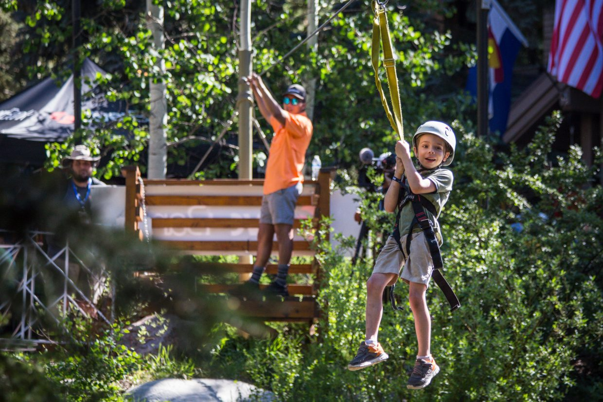 Benjamin VanLoon of Denver, Colo., smiles as he zips across Gore Creek at the GoPro Mountain Games on Saturday in Vail. Local business, Zip Adventures, featured a short sample zipline for attendees of the Mountain Games.