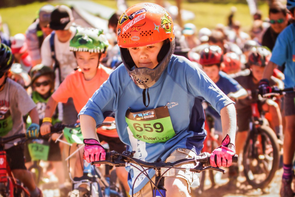 Jackson Fitzergerald, 8, race through the start line of the Kids Mountain Bike Competition at Golden Peak on Saturday in Vail. The games wrap up today
