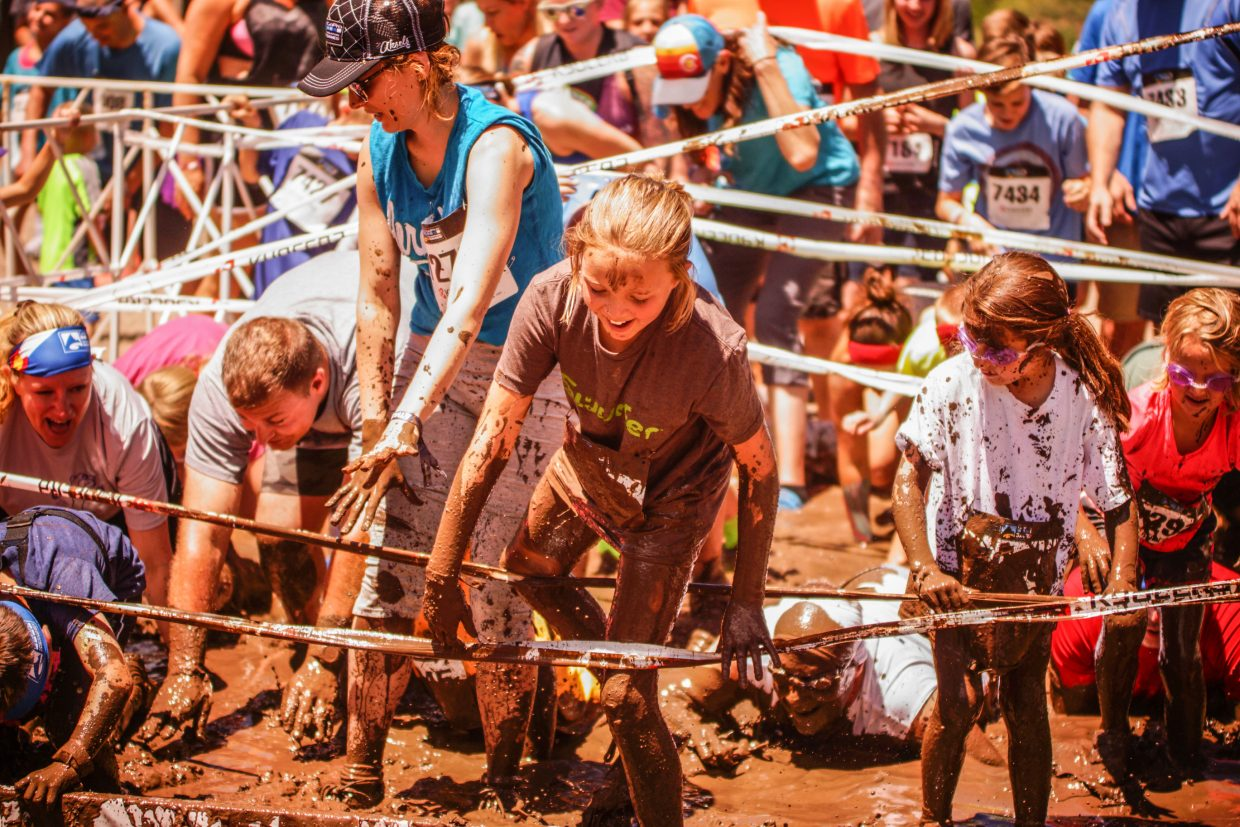 Competitors race through a mud pit during the Kids and Family Volvo Mountain Mud Run at Gondola One on Saturday in Vail.