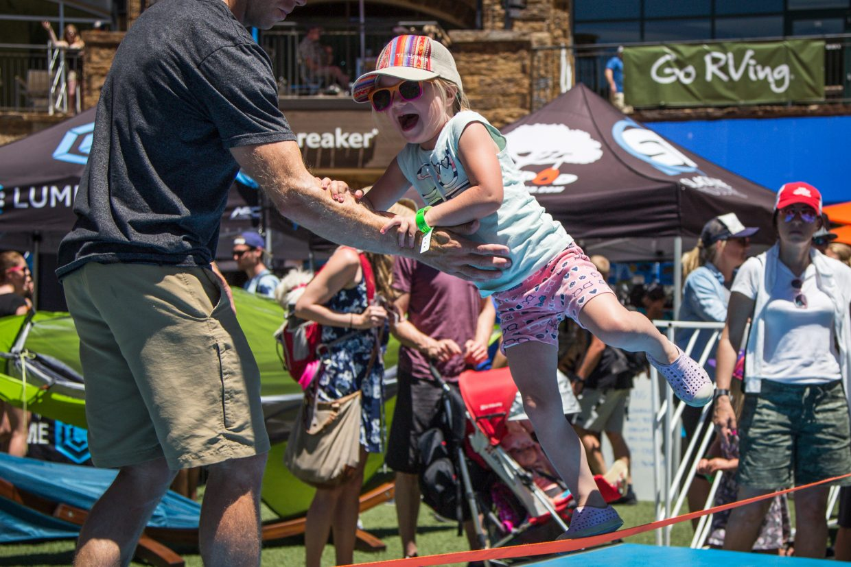 Jordan Johnson grasps her dad Robert Johnson's arm as she attempts to walk the slackline at the GoPro Mountain Games on Saturday in Vail. The Mountain Games encourage all levels of abilities to get in on the action over the weekend.