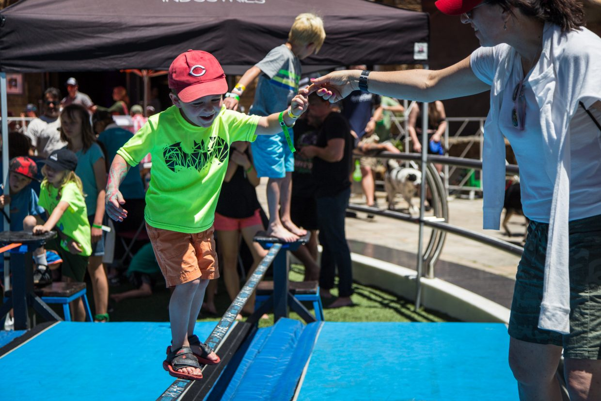 Cauley Mettler holds onto Toni Mettler's arm as he attempts the slackline at the GoPro Mountain Games on Saturday. Familes and athletes alike gathered to watch and participate over the weekend.