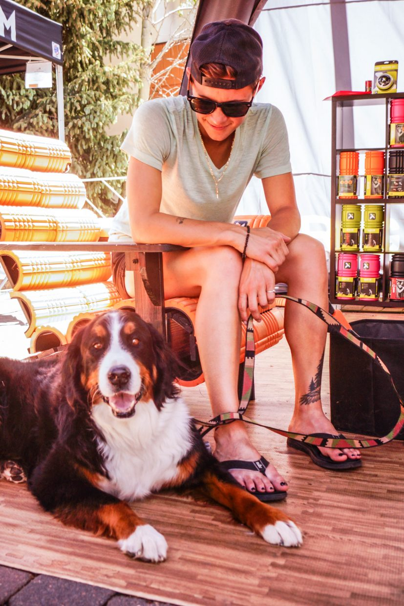 Hali Groninger and Koda the Bernese Mountain Dog enjoy the shade at the Trigger Point tent on Sunday in Vail.