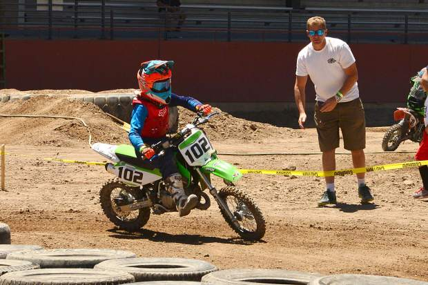 No. 102 Tiegan Stiebel, of Eagle, powers around the tire section of the track in the 65cc 8- to 11-year-old class while father Guy Stiebel cheers him on at Moto Mayhem at the Eagle County Fairgrounds on Saturday.