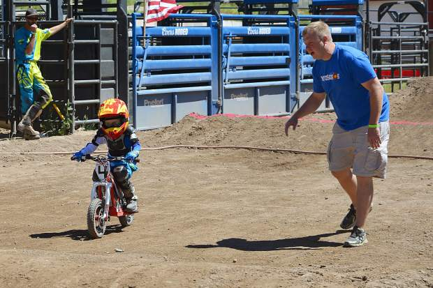 Sporting bib No. 4, Hayden Hyslop, 4, of Edwards, gets some coaching from his father, Travis, to slow down in the upcoming whoops section of the track at Moto Mayhem at the Eagle County Fairgrounds on Saturday.