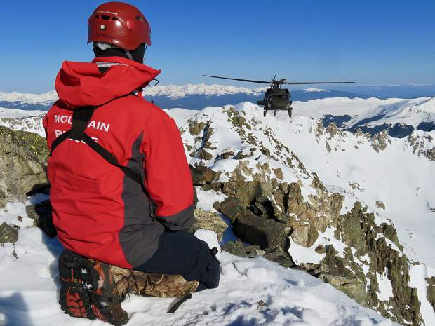 A Summit County Rescue Group team member awaits the arrival of a Blackhawk helicopter provided by the Army National Guard based in Eagle on Monday morning to help two stranded climbers off Quandary Peak.