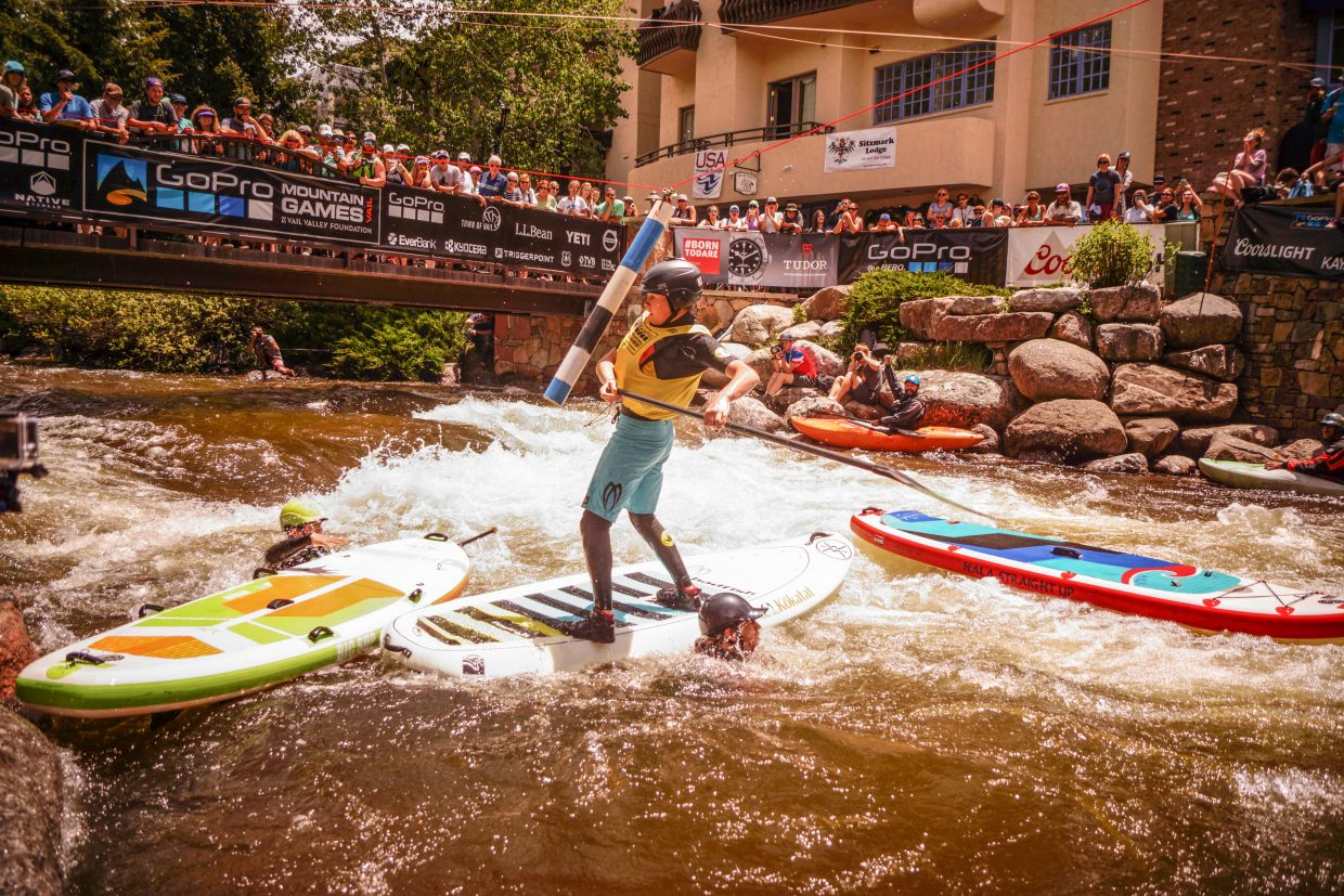 Miles Harvey, 14, holds on while his competitors swim to get back on their boards, during the SUP Cross competition on Sunday in Vail.