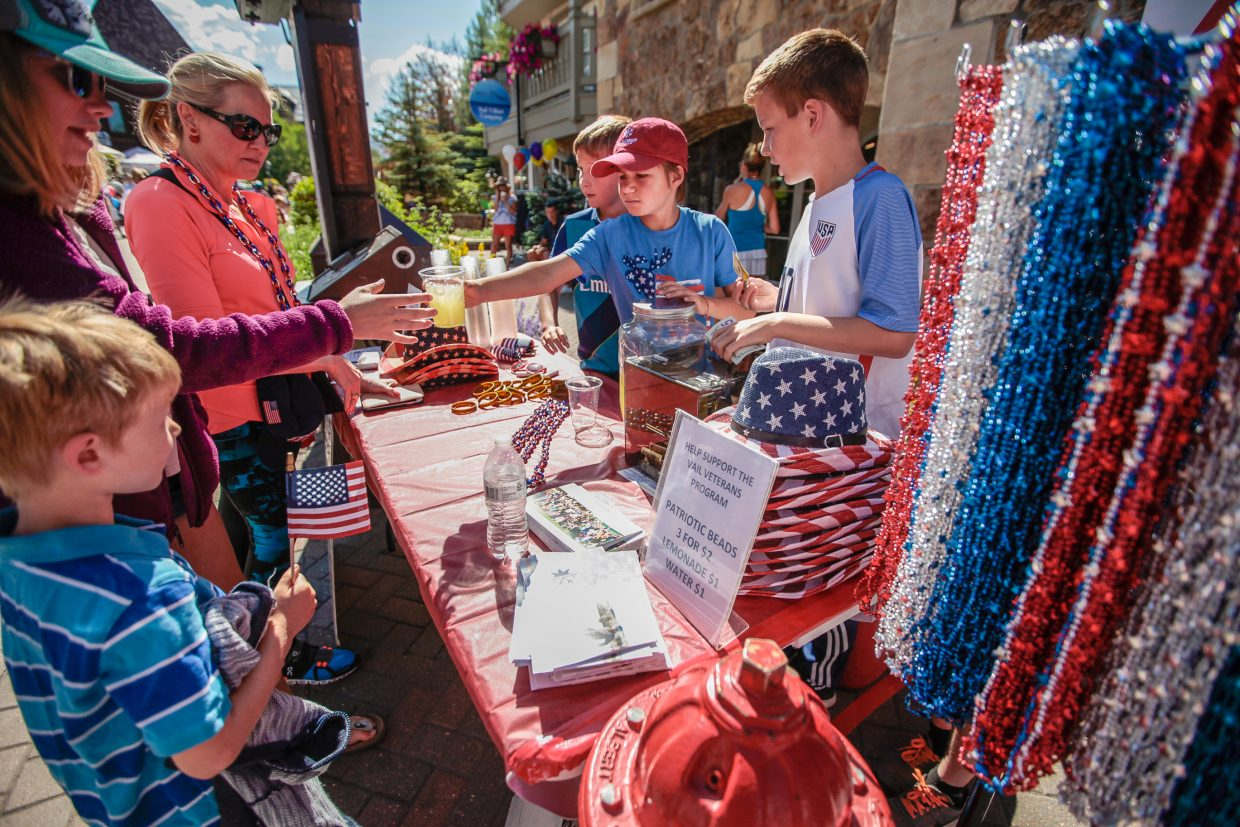Teddy Bruno hands out lemonade while Charlie Precourt and Griffin Moore help other costumers while volunteering for the Vail Veterans Program during the July 4 parade in Vail.