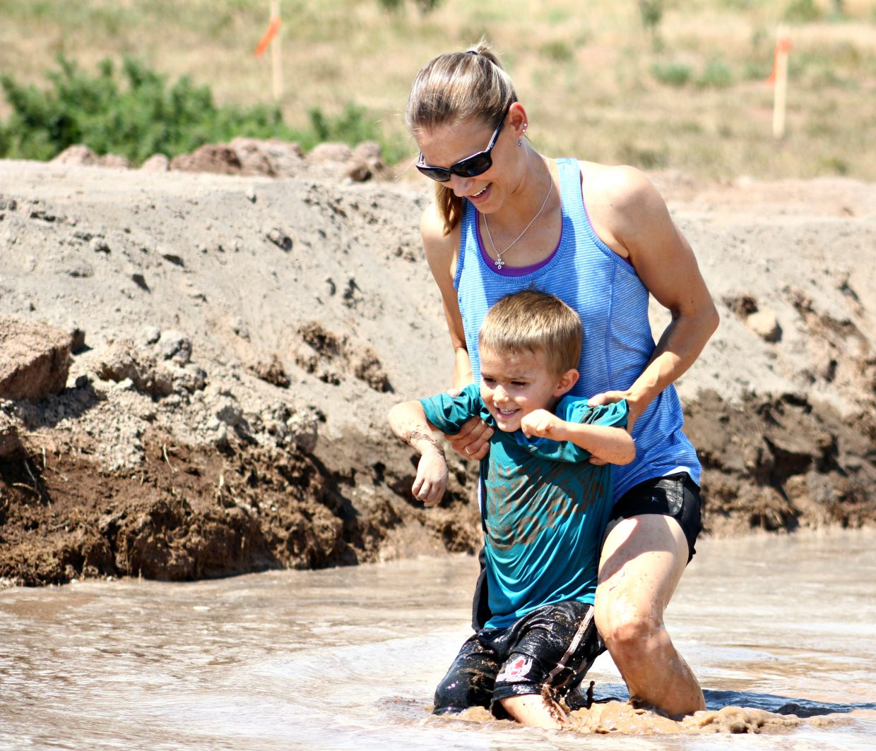 Lindsay Littlepage carries her son, 4-year-old Jacob, through a deep trench of mud. Mudzilla was presented by Scott Green Excavating, 7 Hermits Brewing Co., the town of Gypsum and Western Eagle County Metropolitan Recreation District.