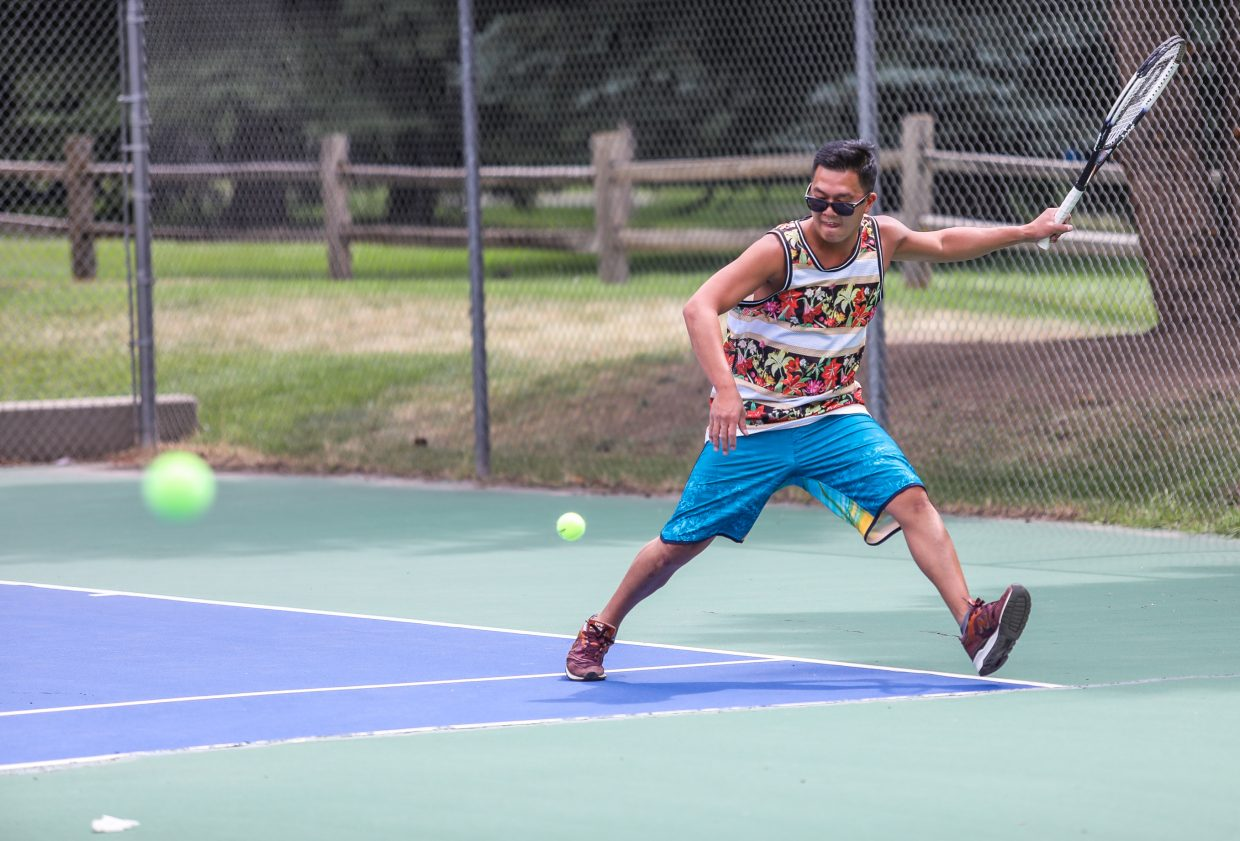 Phuc Tran of Avon works on his forehand in a game of tennis Sunday in Avon. Rain is expected for the next few days before drier weather returns.