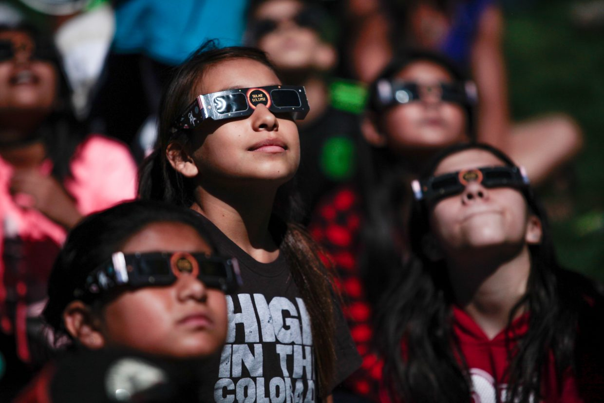 Kids look at the solar eclipse Monday in Avon. Special glasses are needed to view the eclipse.