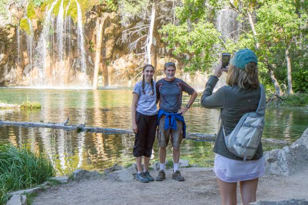 Paul and Anna Johnston from Wisconsin get their photo taken in front of Hanging Lake on Tuesday morning.