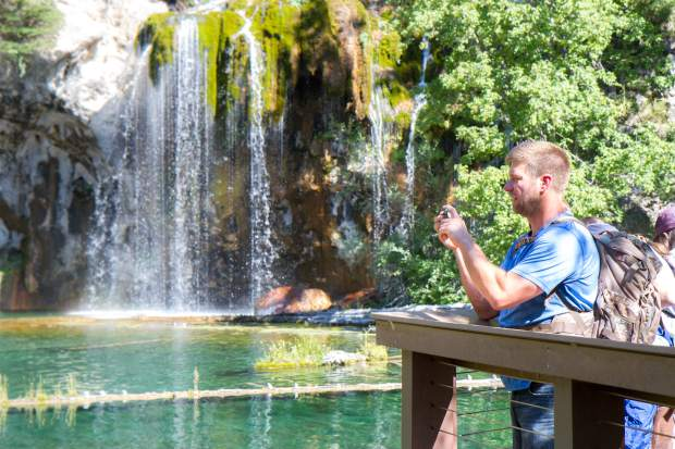 Alan Brekke from Minnesota takes a photo Tuesday morning of the cyrstal clear water at Hanging Lake.