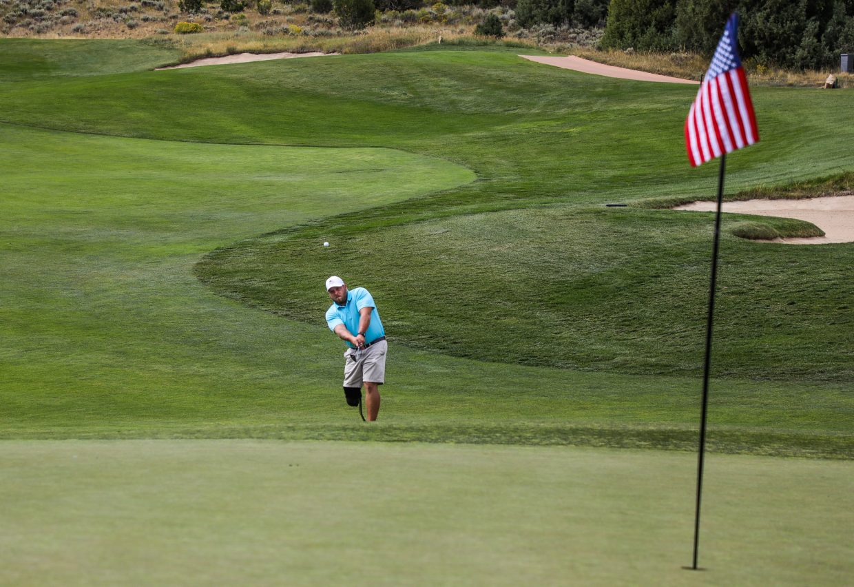 Ryan Wilcox, Army, chips to the green during the Vail Veterans Program Thursday at Red Sky Golf Club. The green flags on the Fazio Course were changed to American flags.