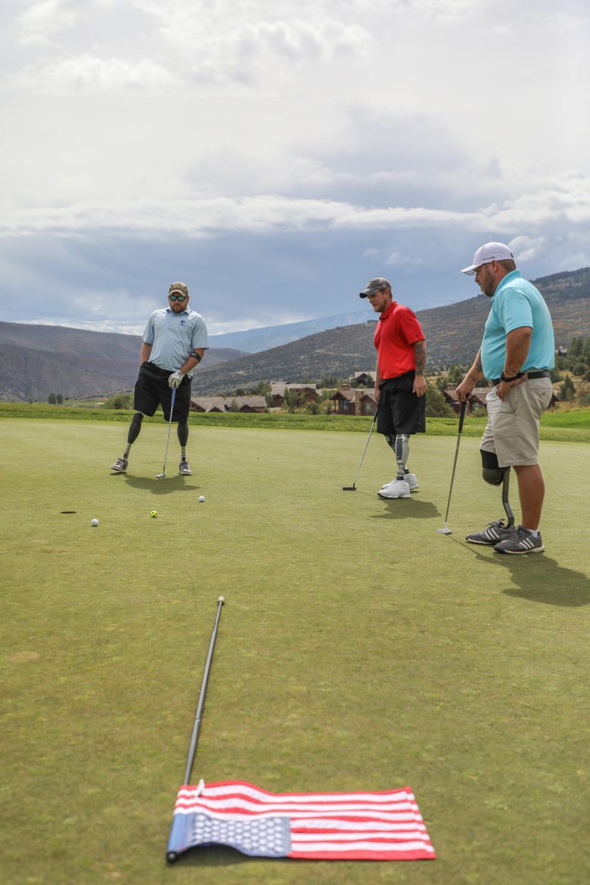 From left, Matt Parker, Tim Johannsen and Ryan Wilcox put on the first green during the Vail Veterans Program Thursday at Red Sky Ranch and Golf Club.